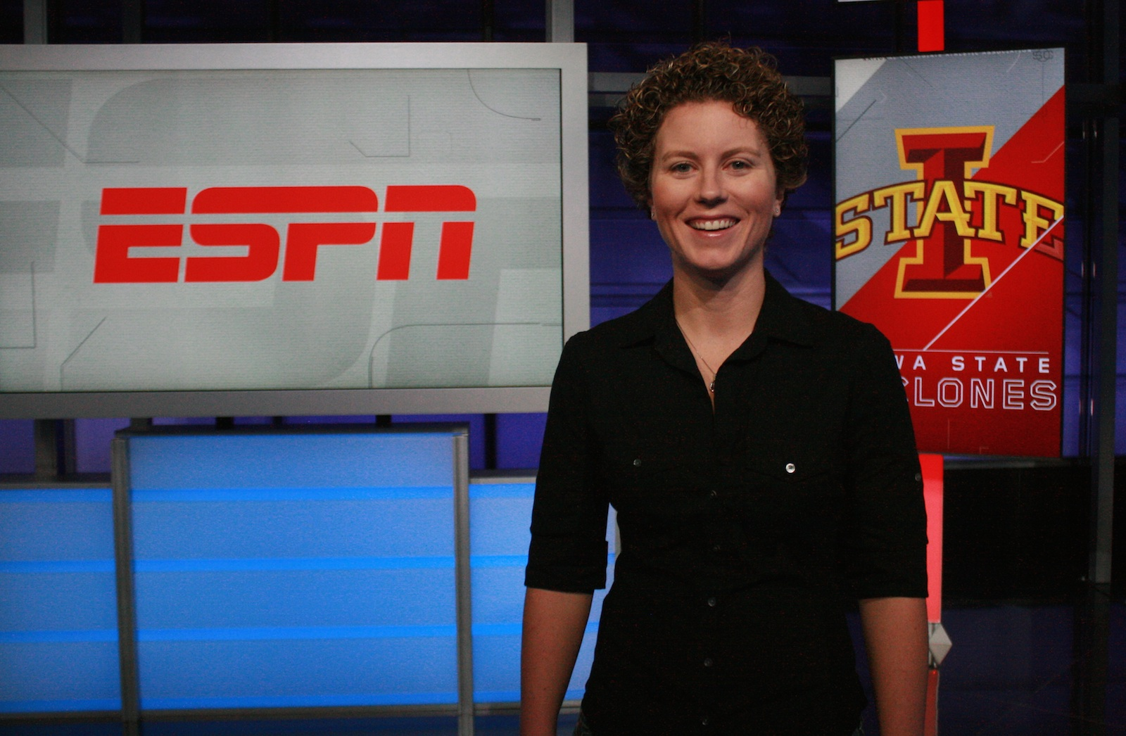 Emma Reed on set at ESPN with digital signs displaying the ESPN logo and Iowa State logo behind her.