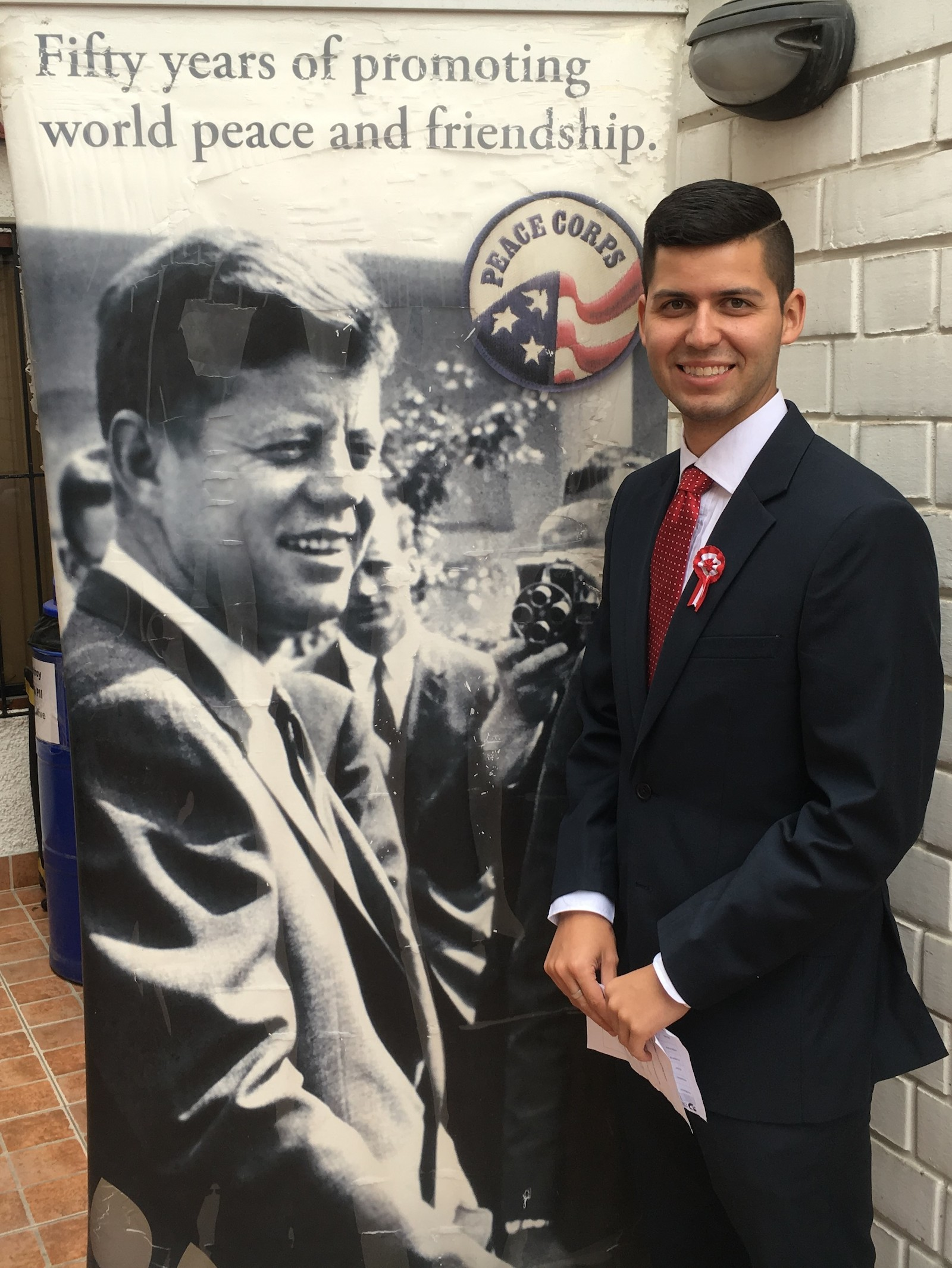 Nick Morton stands in front of a Peace Corps banner illustrated with a photo of President John F. Kennedy.