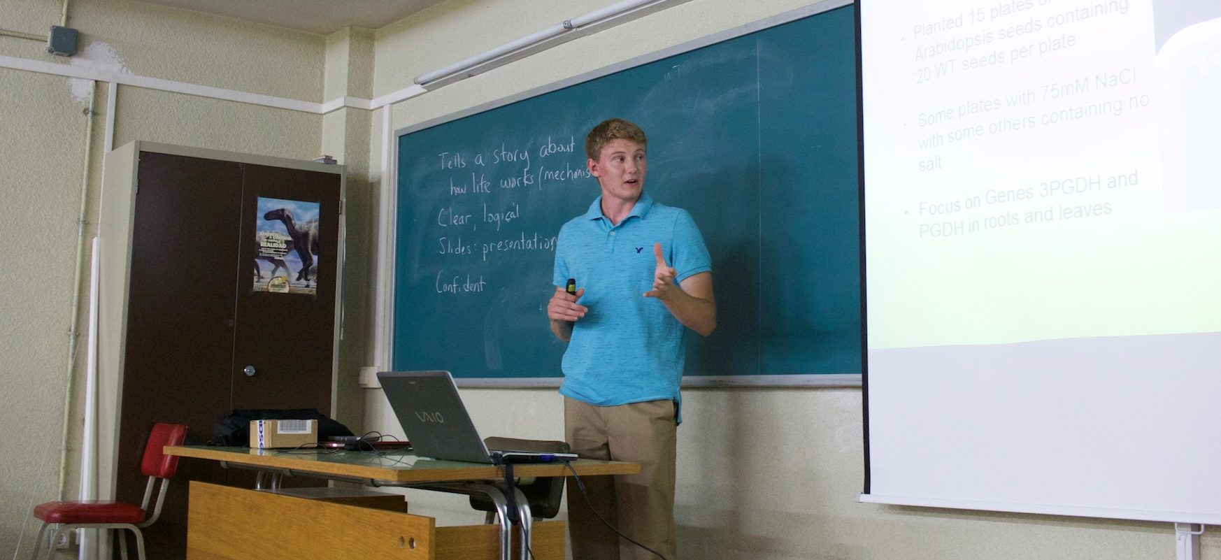 Student Dirk Winkelman stands in front of a chalkboard in a University of Valencia classroom. His laptop displays a presentation of his plant research on the screen to his left.