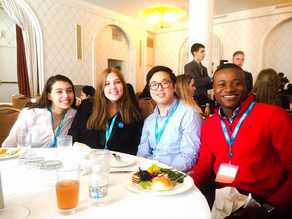A group of four students seated at a round table for a UNICEF luncheon.
