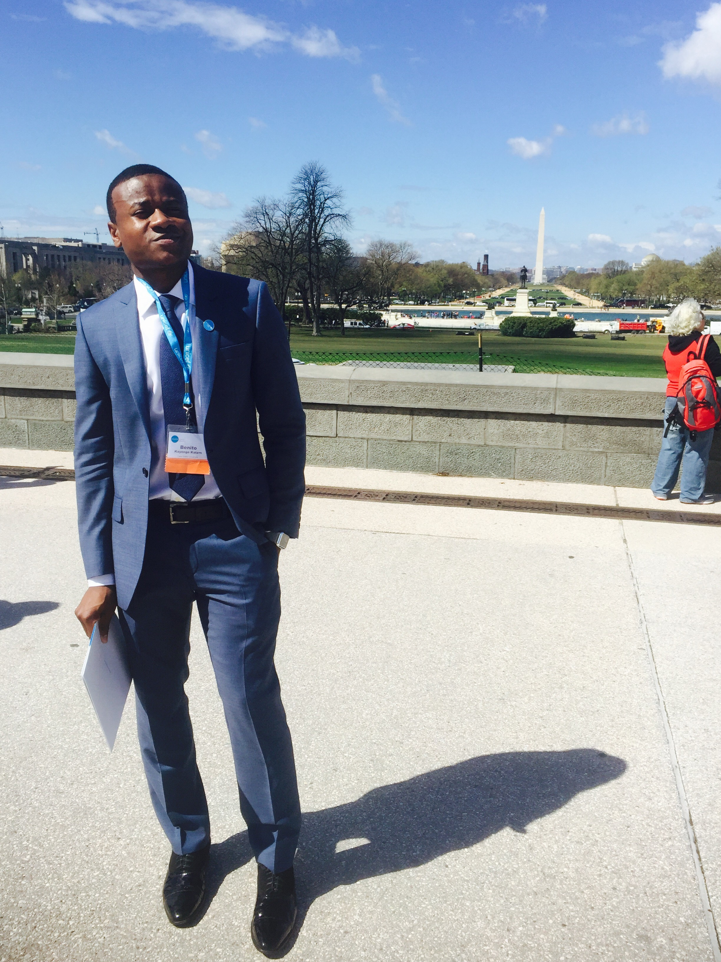 Benito Kayenge stands outside in Washington D.C. with the National Mall in the distance.