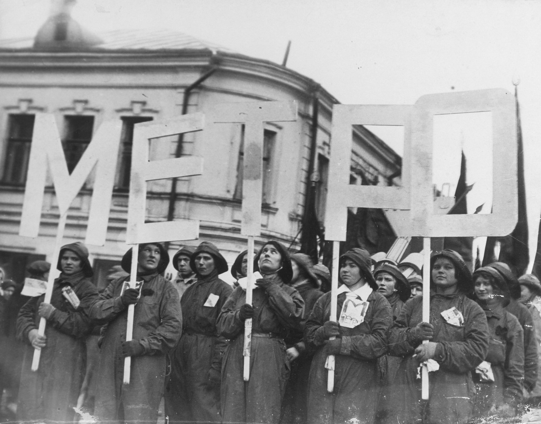 "A group of women hold letters that spell out ""Metro"" while marching in a parade in Moscow."