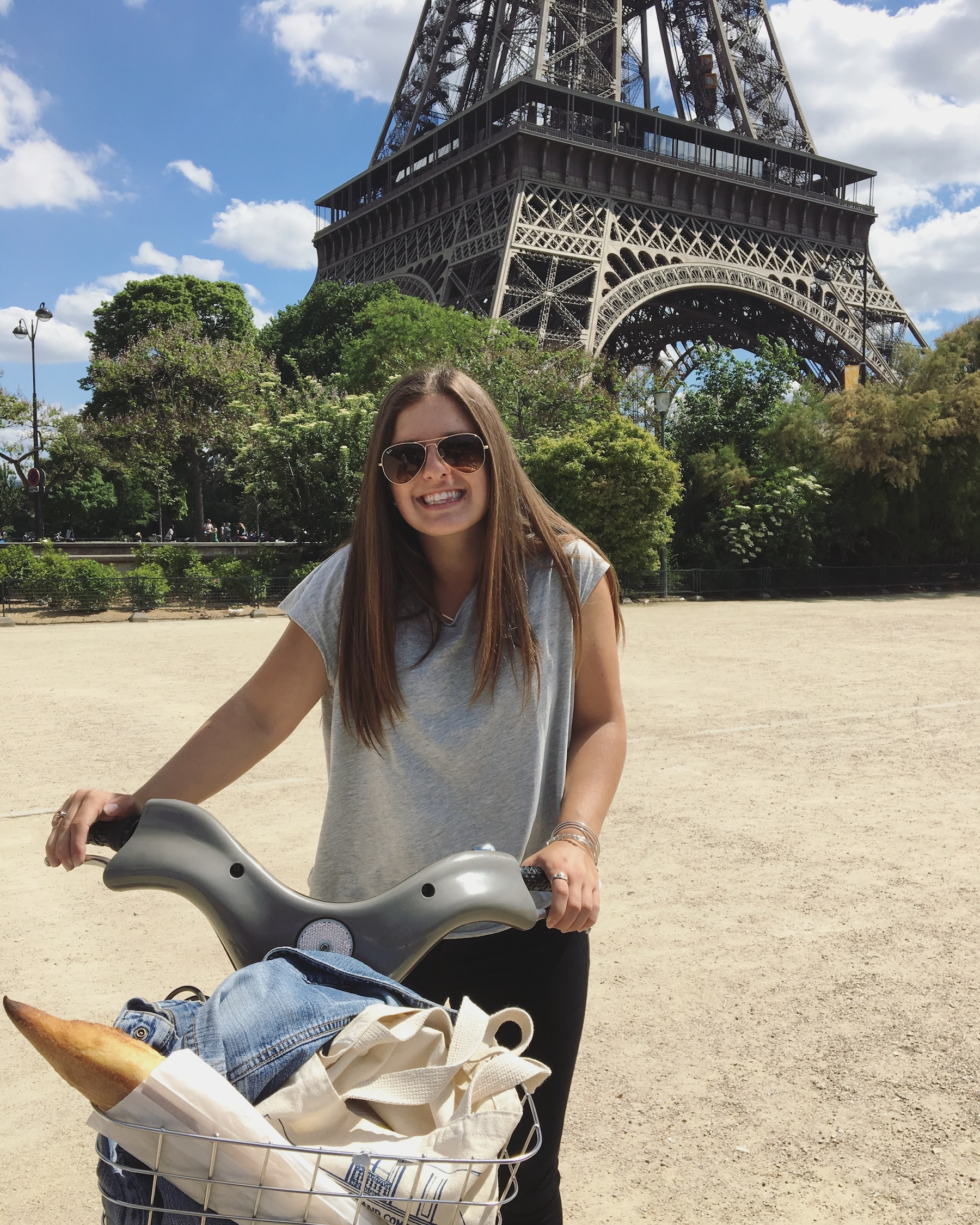Student Natalie Weidner poses on a bike in front of the Eiffel Tower on a study abroad trip to Paris, France. The metal basket on the front of her bicycle contains a french baguette.