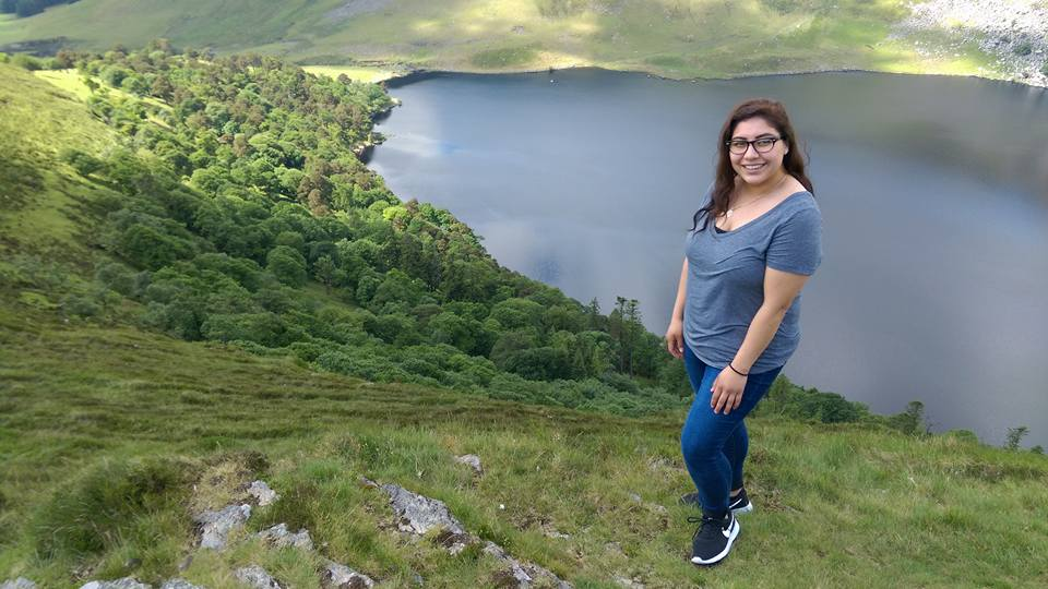 Student Rosita Cansino stands in front of Lough Tay (Guinness Lake) in County Wicklow. The blue lake is surrounded by lush green vegetation.