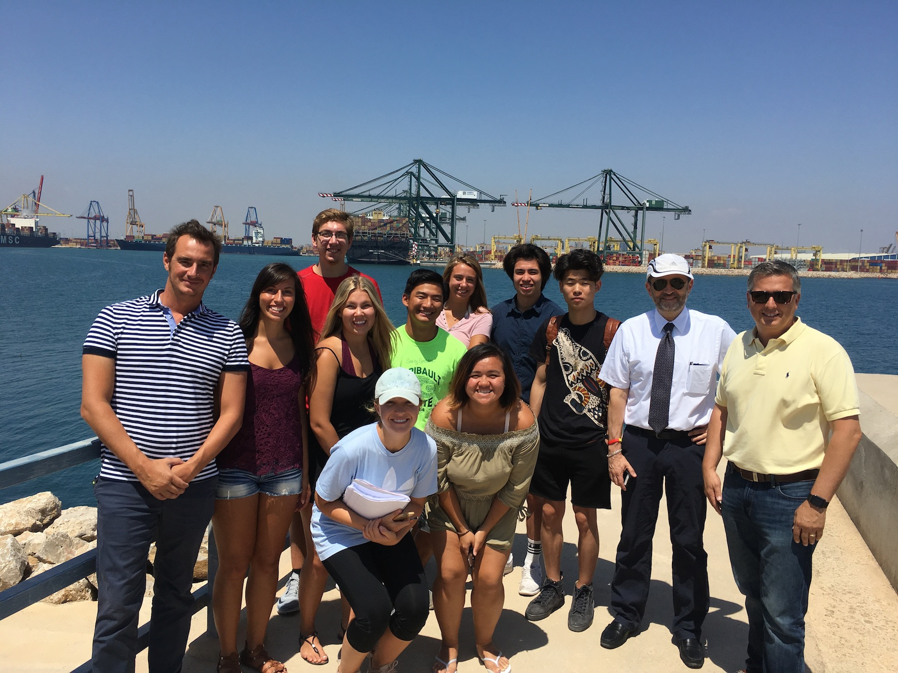 Twelve Iowa State students and faculty pose on a dock in front of the Port of Valencia with the sea and commercial ships in the background.