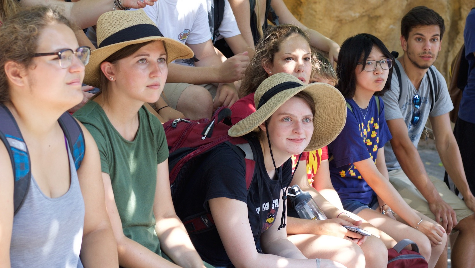 Six Iowa State students are seated in a rock area at Bioparc Valencia, a zoo in Valencia, Spain.