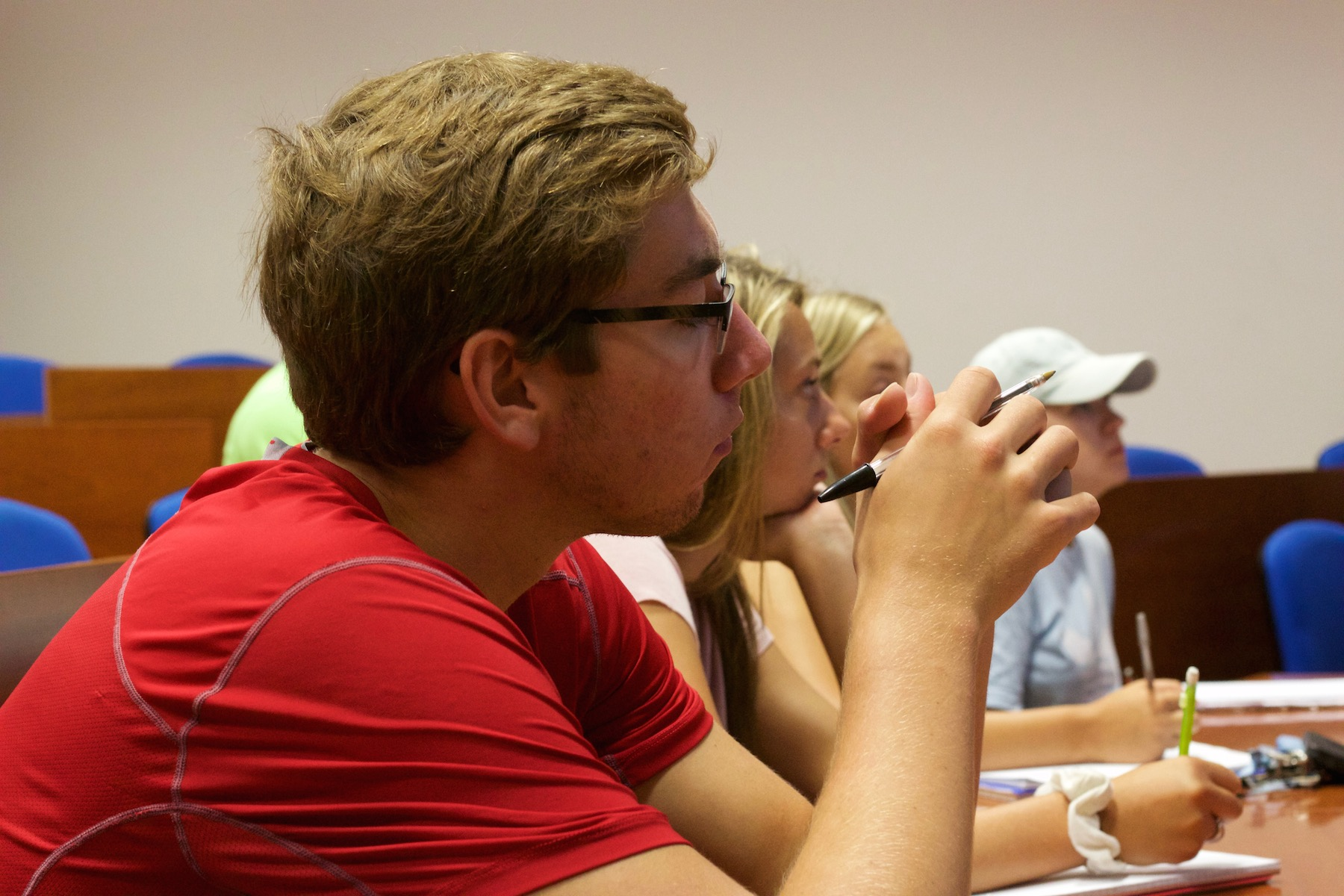 Four Iowa State students sit at desks listening to a class lecture during study abroad.