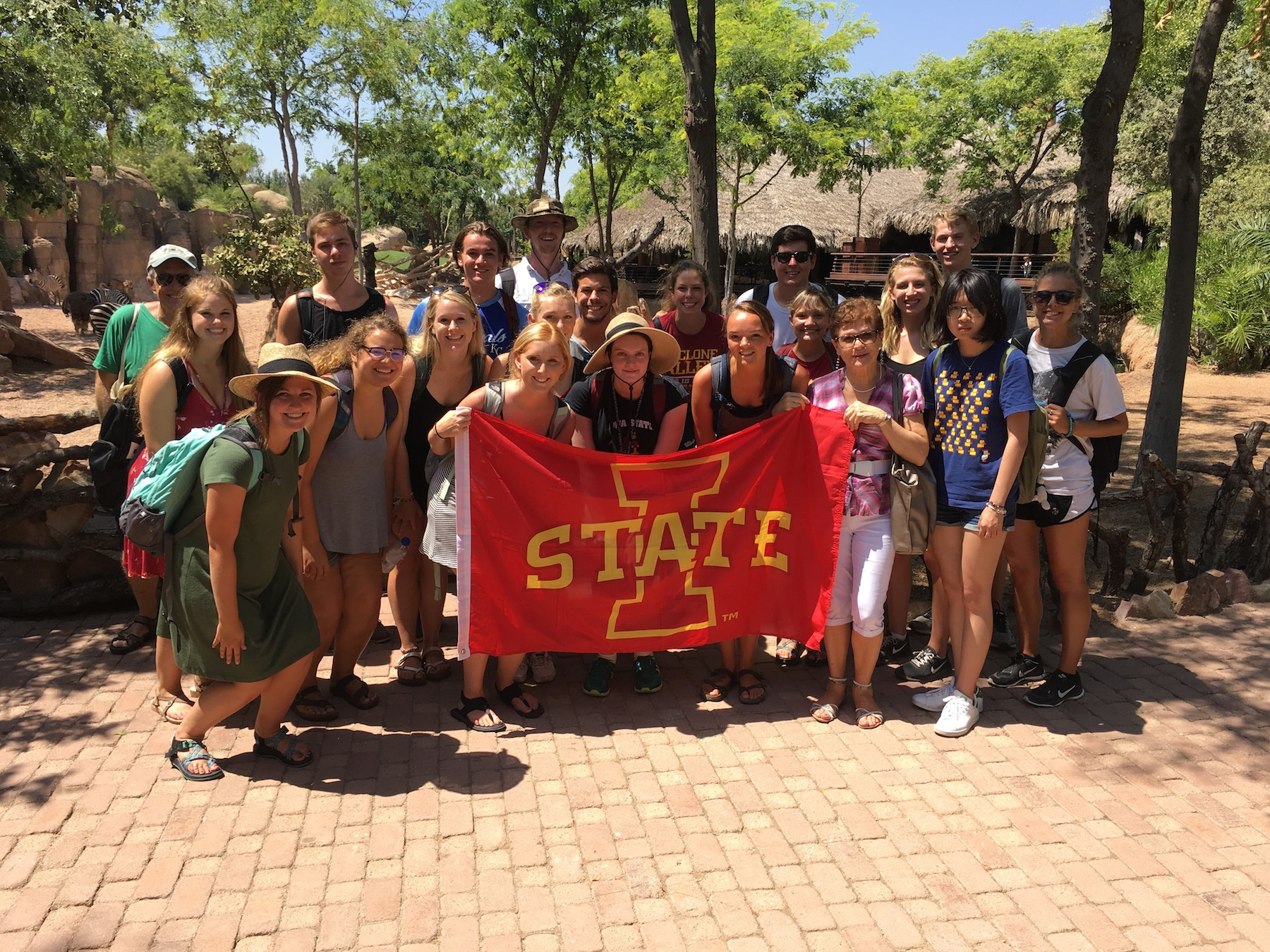 A group of Iowa State students in the Summer in Valencia study abroad program hold a red Iowa State flag while standing in front of a Valencia zoo exhibition.