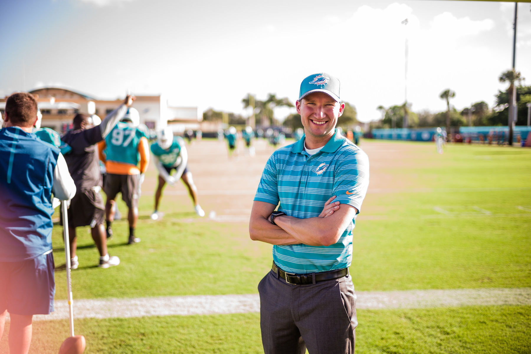 Dennis Lock stands with arms crossed on the practice field for the Miami Dolphins. Dolphins players are in the background doing practice drills.