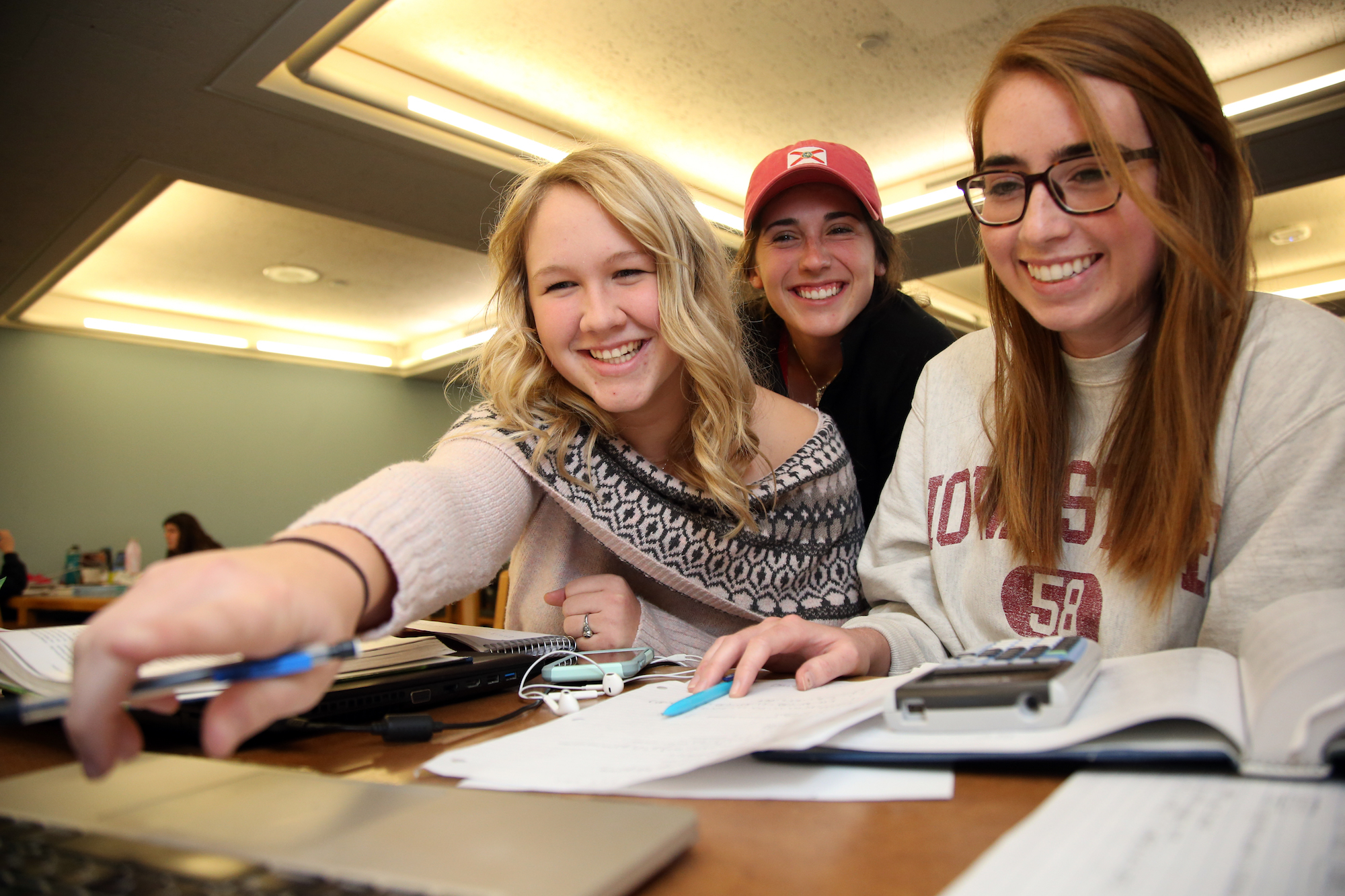 Anna and two other students point toward a computer while looking over textbooks and notes.