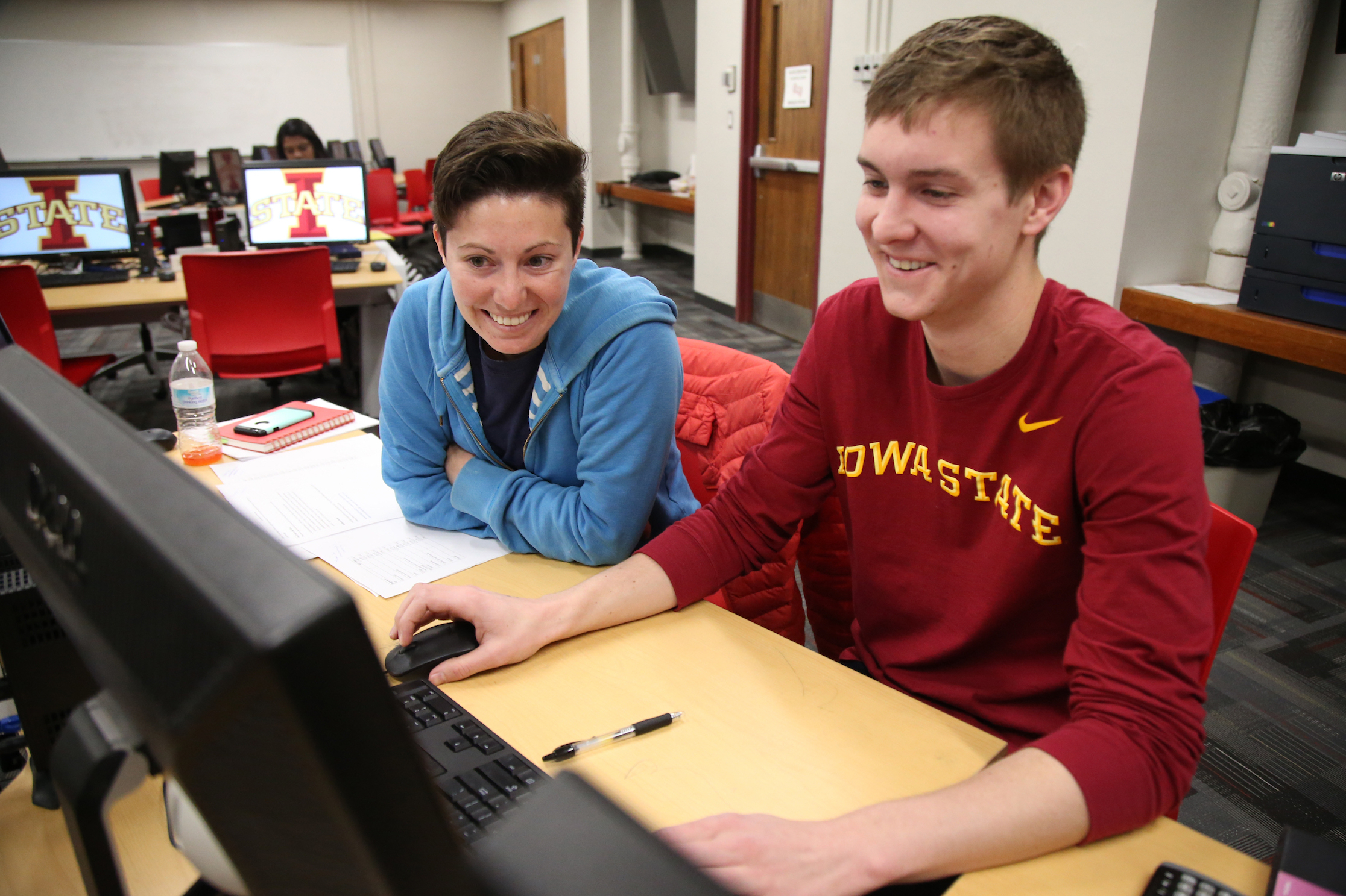 Two students work at a desktop computer together.