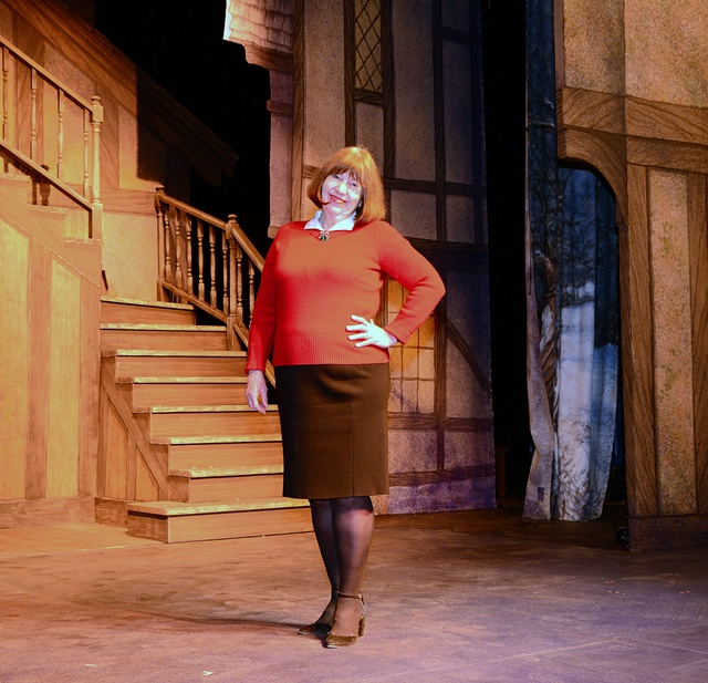 A woman standing on center stage in Fisher Theater with a stairs and set scenery behind her.