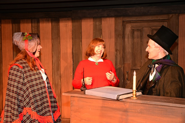 A faculty member talks with two students who are in costume on a stage set.