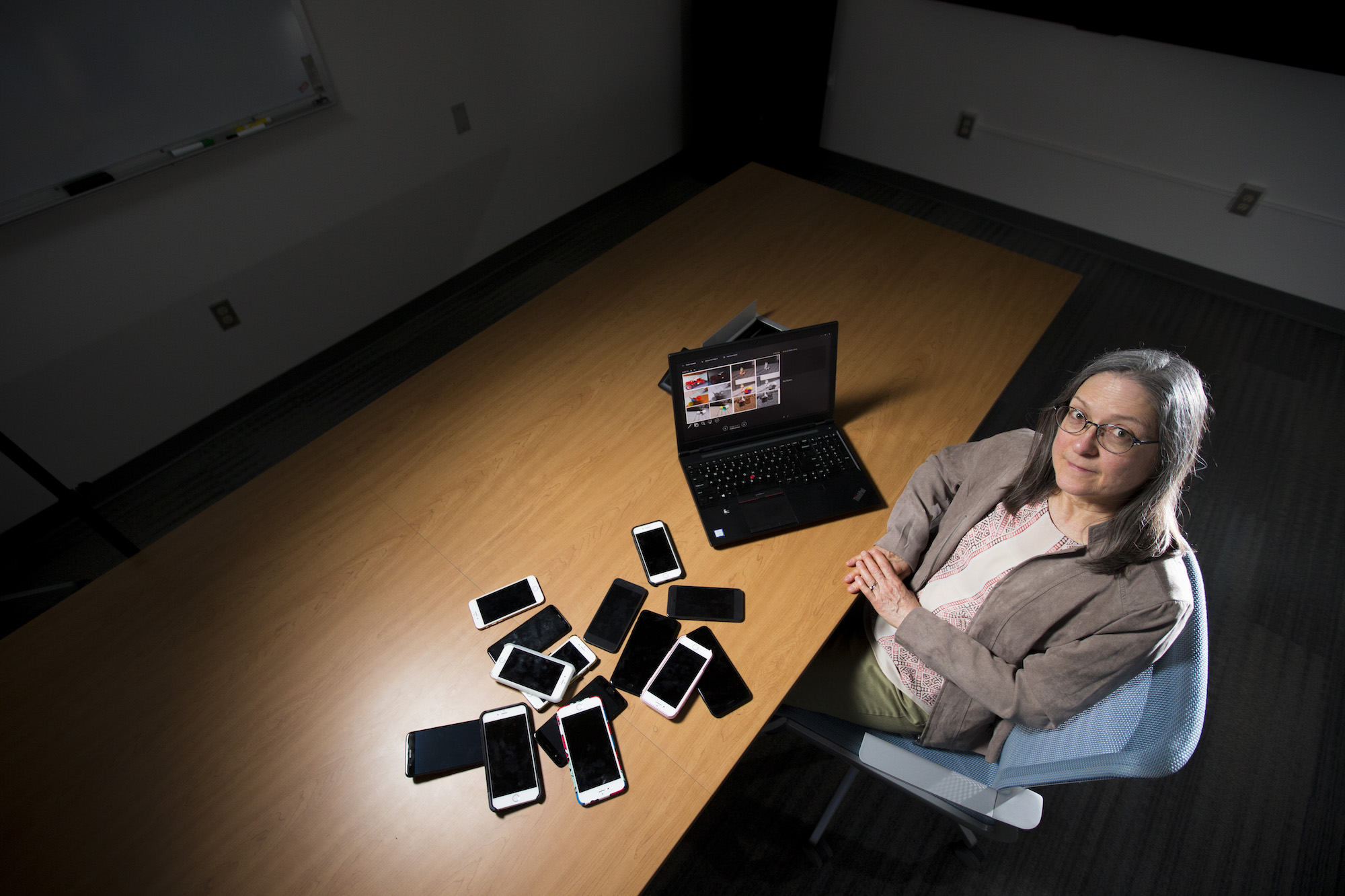 Looking down at Jennifer Newman next to her laptop and a pile of mobile phones.