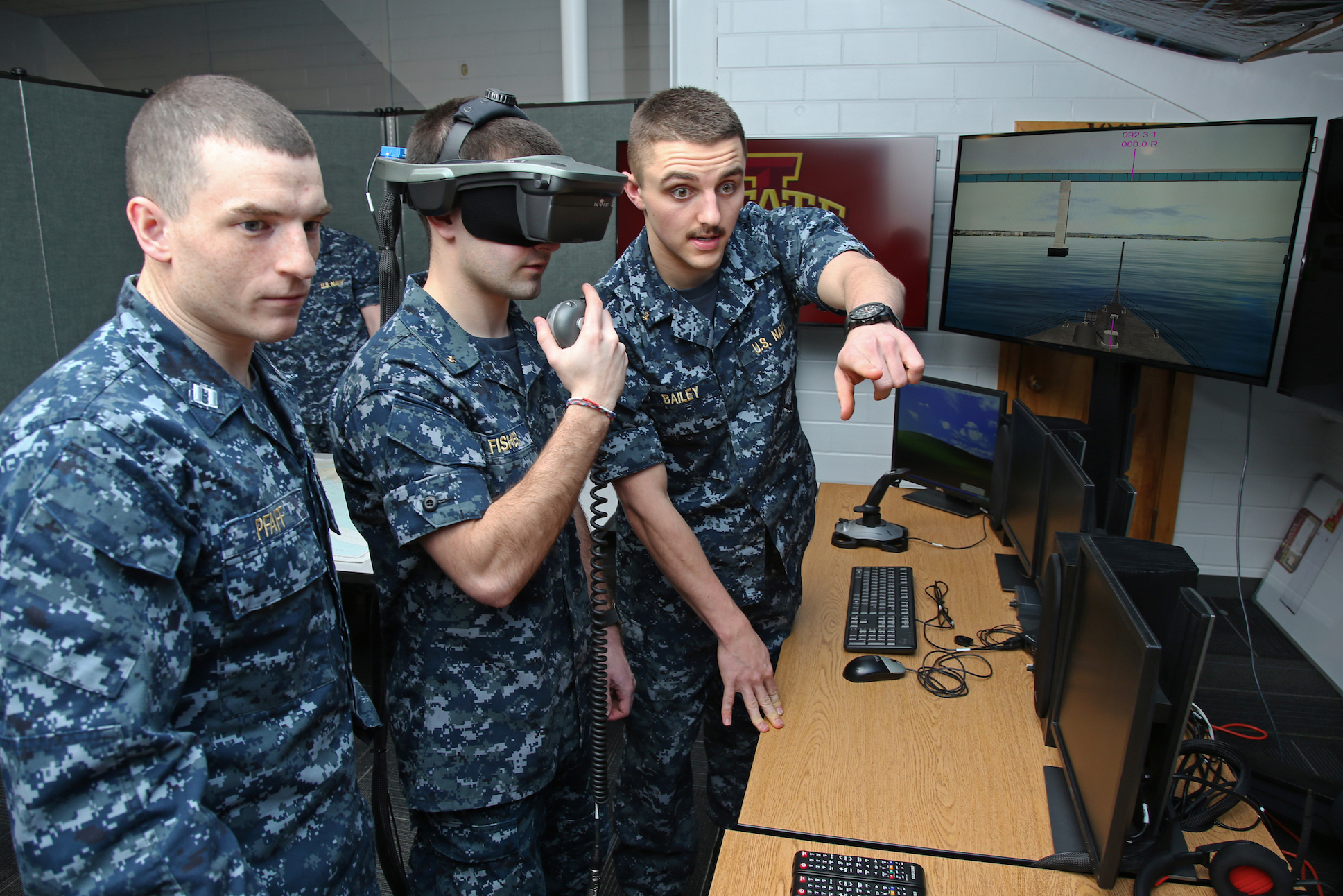 A Navy ROTC midshipmen wears the virtual reality headset while another midshipmen and instructor look on.