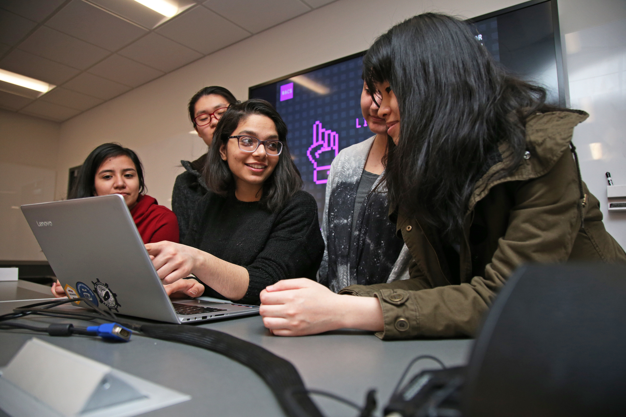 A group of women huddles around a computer.