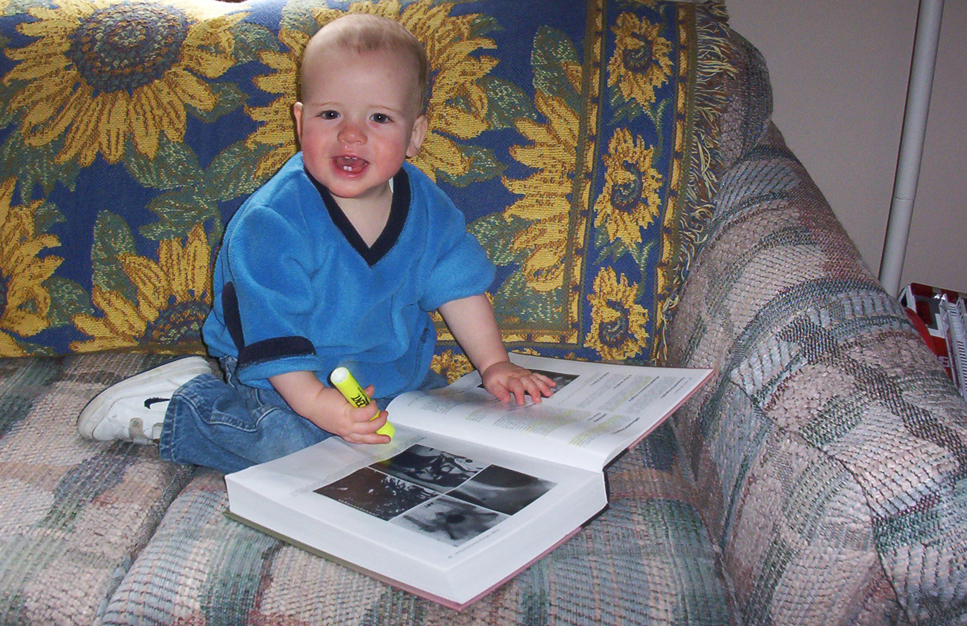 A baby sits on a couch with a highlighter and textbook.