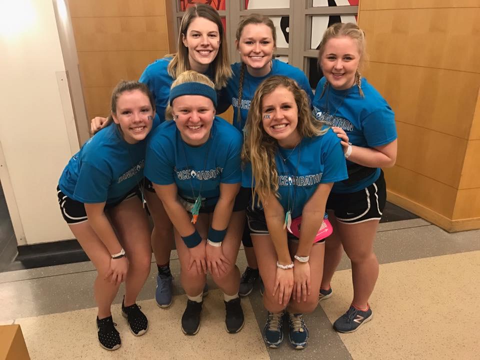 Six women pose in blue shirts.