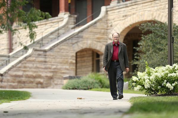 Mack Shelley walking in front of Catt Hall on Iowa State University