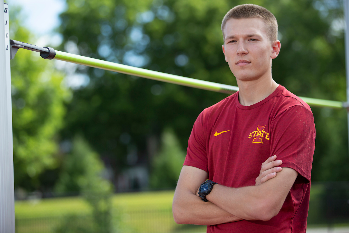 A portrait shot of Cody Gannon by the high jump bar.