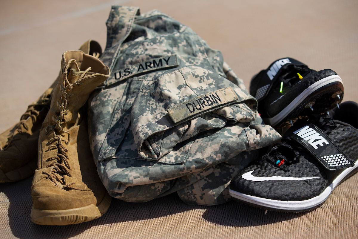 A still photo of Army boots, an Army uniform, and track shoes.