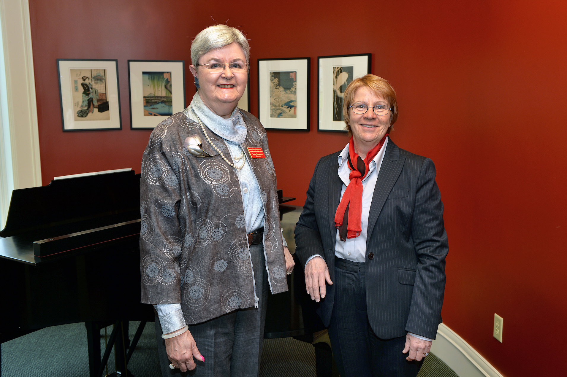 Two women in front of a piano.