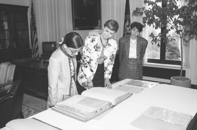 Three women look at records on a table.