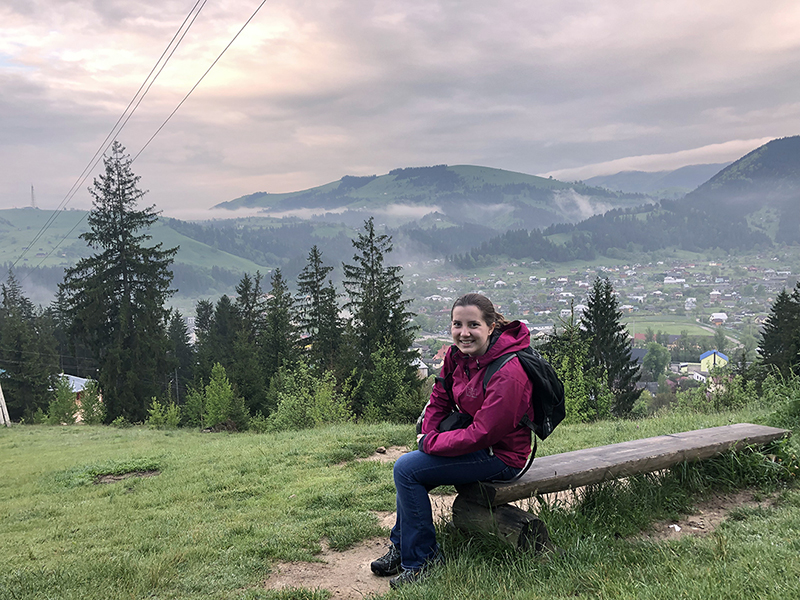 Student sits on a bench on a mountain in Lviv