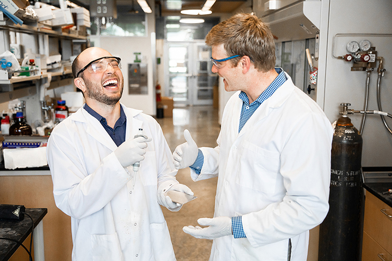 Brett VanVeller and his student Luis Camacho laugh as they discuss photochemistry research