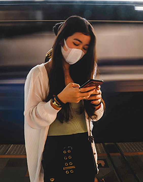 Woman wearing mask using a cell phone.