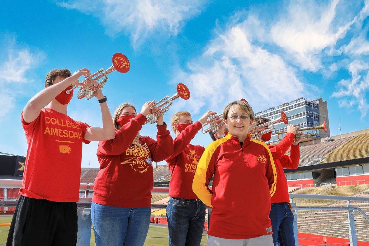 Jen Scharff poses in Jack Trice Stadium with members of the Cyclone marching band