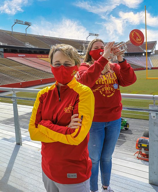 A sweeping view of Jack Trice Stadium, where Jen Scharff poses in front of Iowa State student Rebecca Gomez, who is playing her trumpet on a beautiful, sunny day