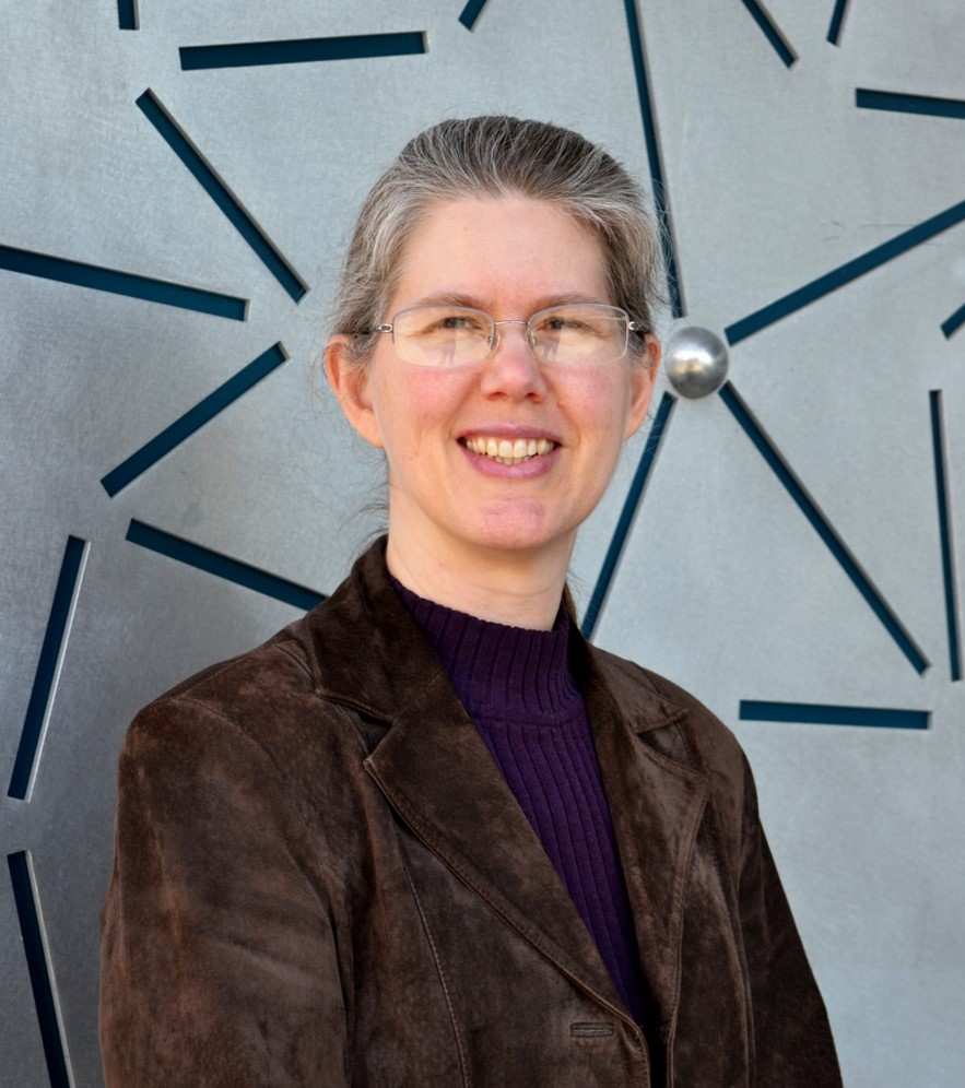 A portrait style photo of Theresa Windus in front of the chemistry building wall.