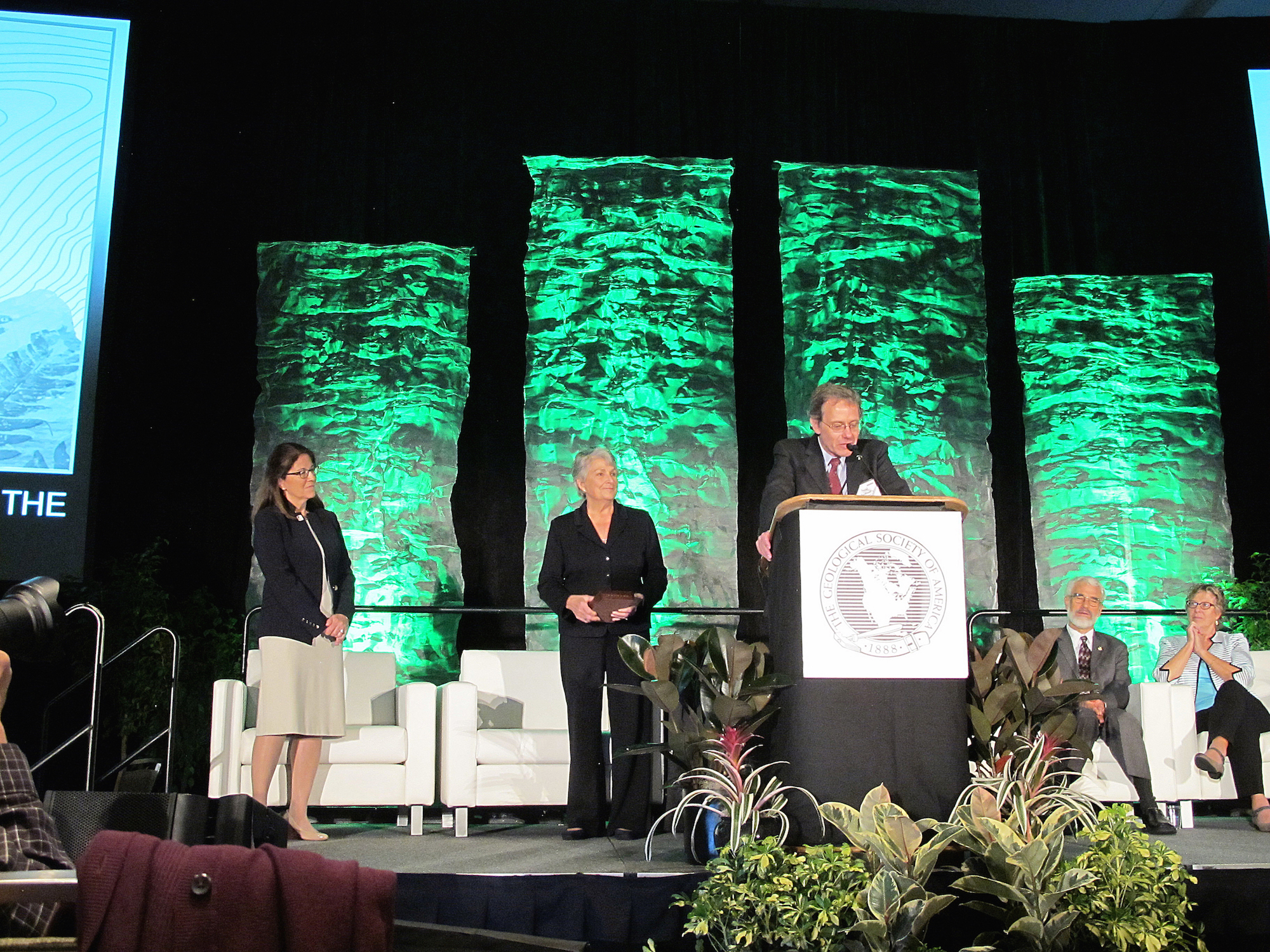 Neal Iverson stands behind a podium and plants on stage. A few people stand or sit in the back of the stage. The backdrop has four green column banners with rock patterns.