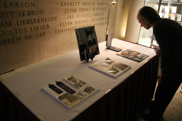 A woman looks at a table holding medals and pictures in Gold Star Hall.