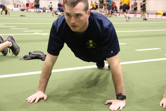 Midshipman Stickelman does pushups on a practice field.