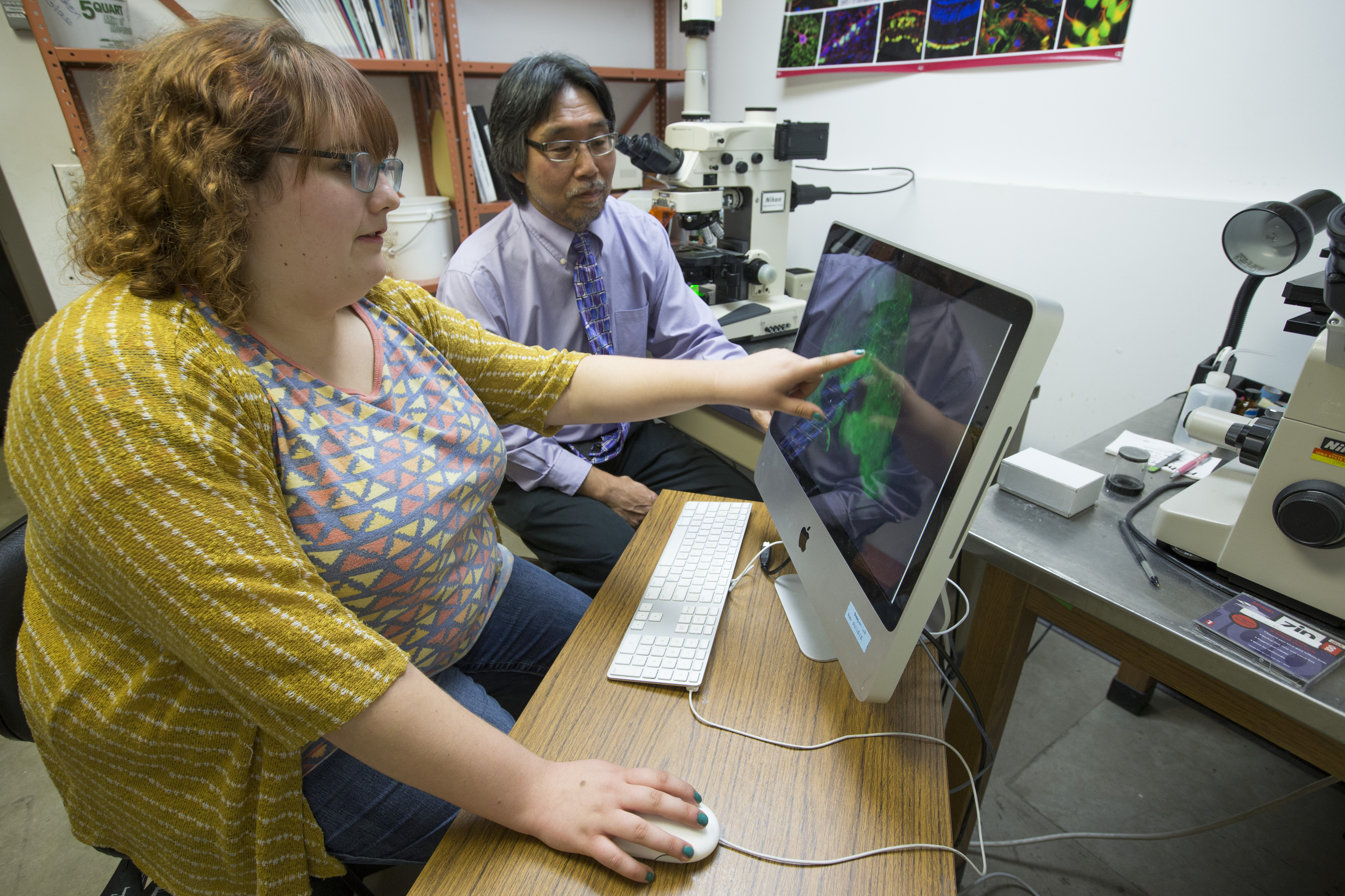 Kaelee Plante points at a computer image while Don Sakaguchi looks on. In the background are microscopes.