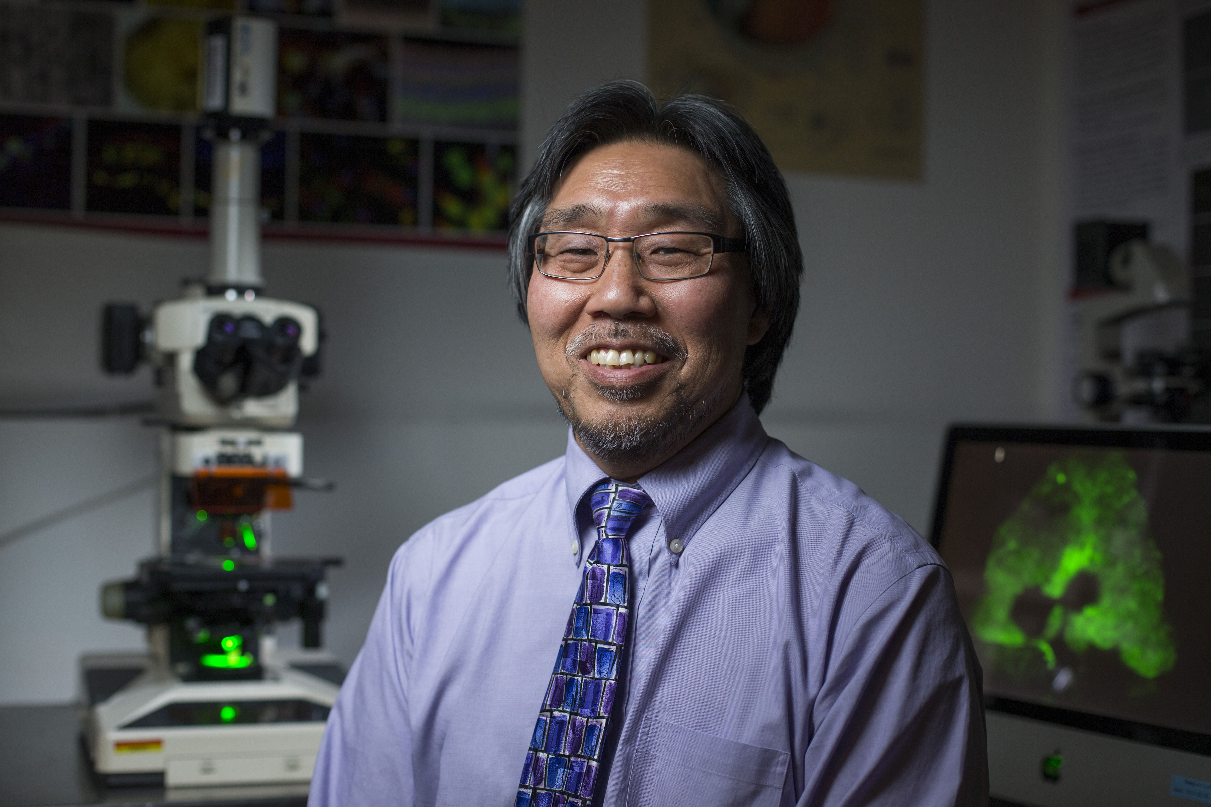 Don Sakaguchi with a microscope and computer imaging behind him.