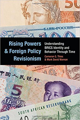 "The cover of the book showing different currencies from different countries and the book title ""Rising Powers and Foreign Policy Revisionism"""