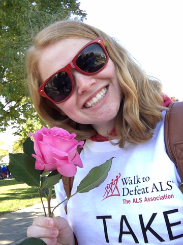 A candid headshot of a student holding a flower