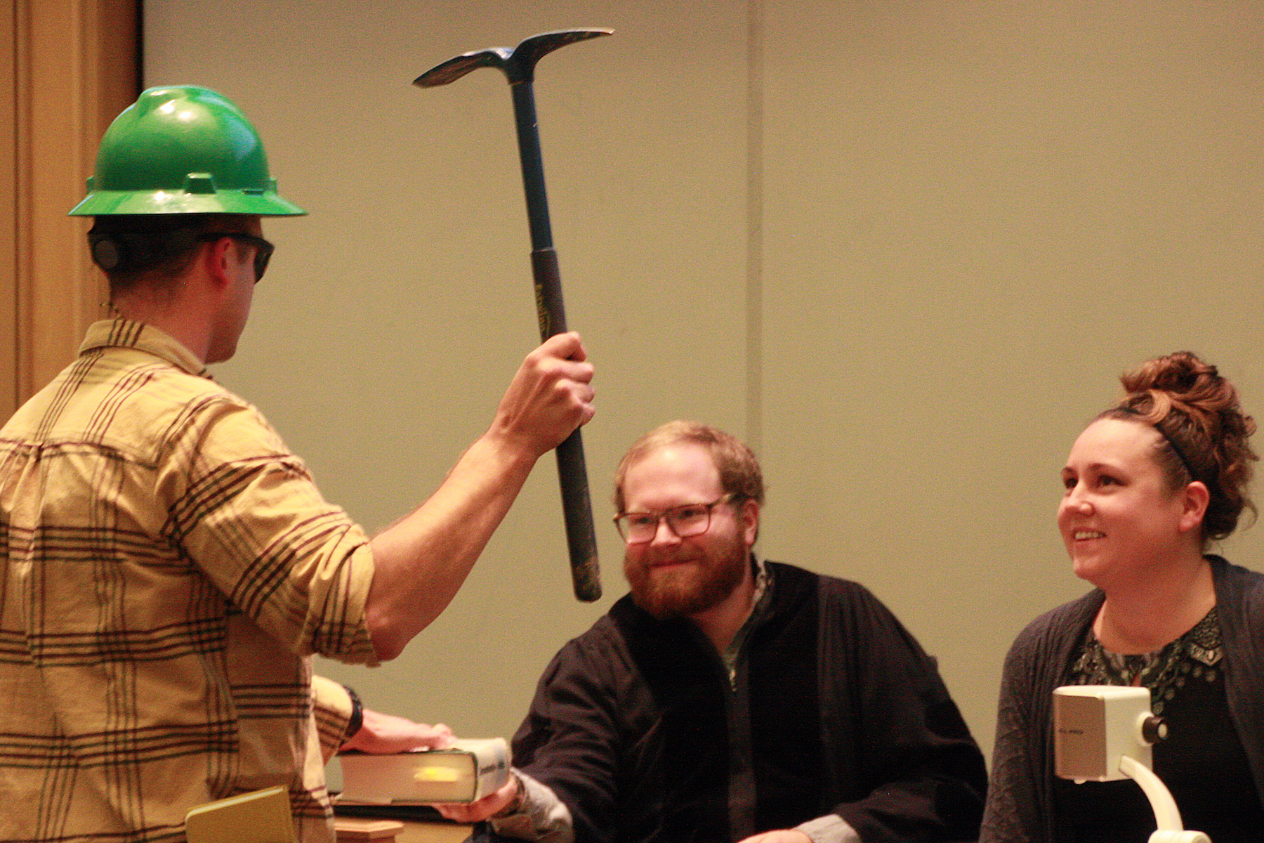 A man wearing a hard hat has his hand on a book and holds a pick-axe while two others look on.
