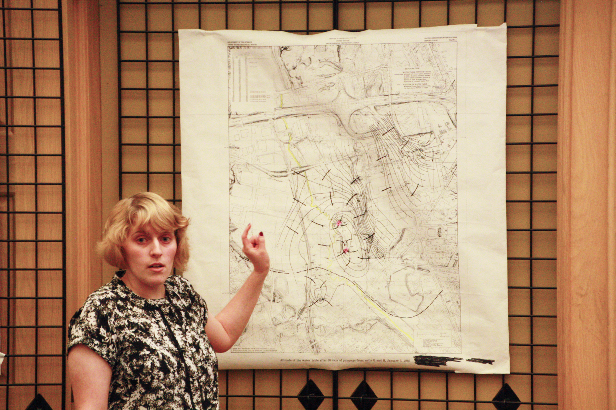 A woman stands in front of a map and points.