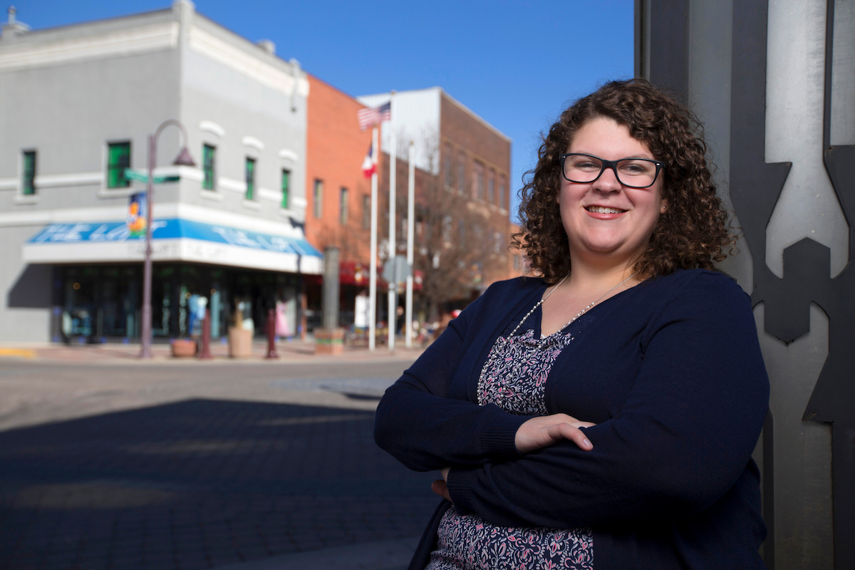 Danielle Propst stands in a community showing a street with shops.