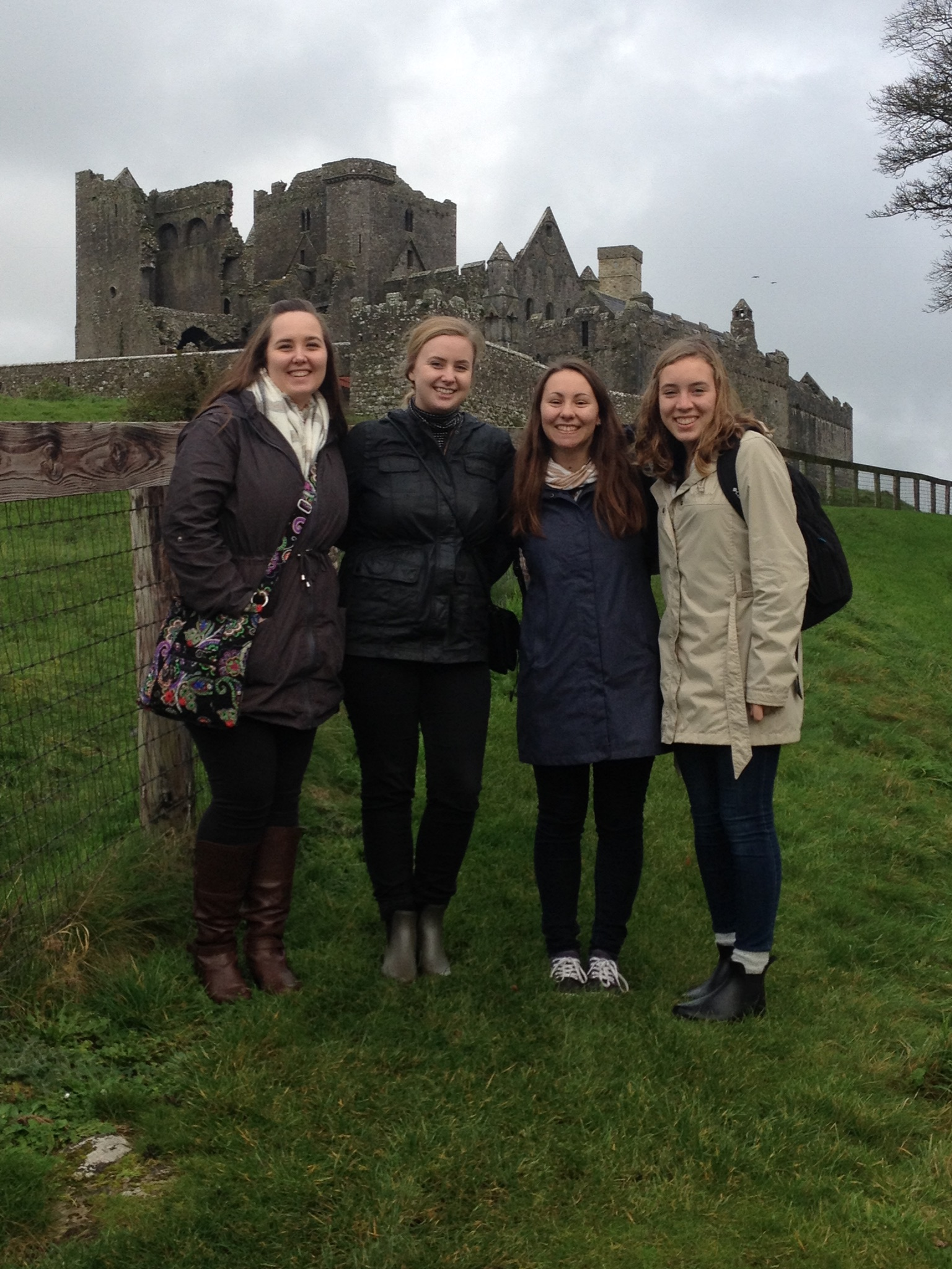 Four students stand in front of a historic site in Ireland.