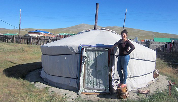 Sarah Hiller stands outside a tent.