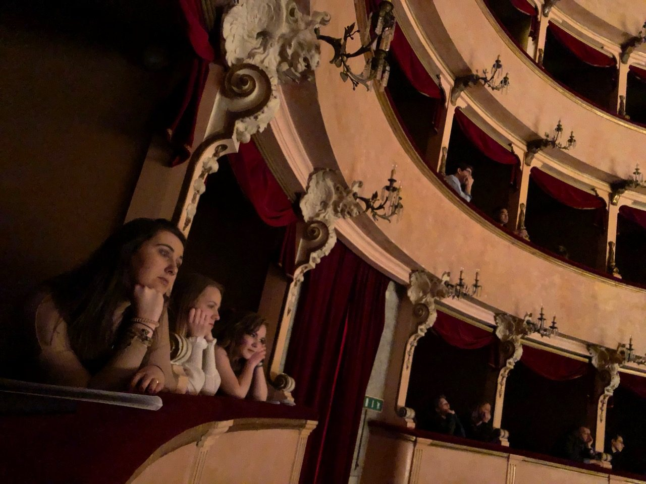 Students sit in the balcony of a theater.