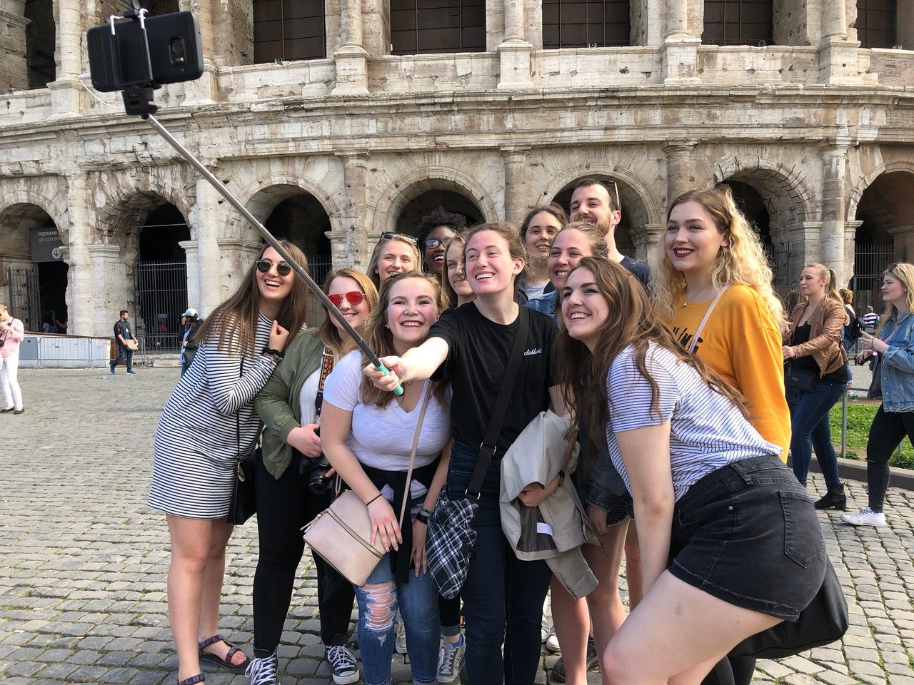 The group takes a selfie in front of the Coliseum in Rome.