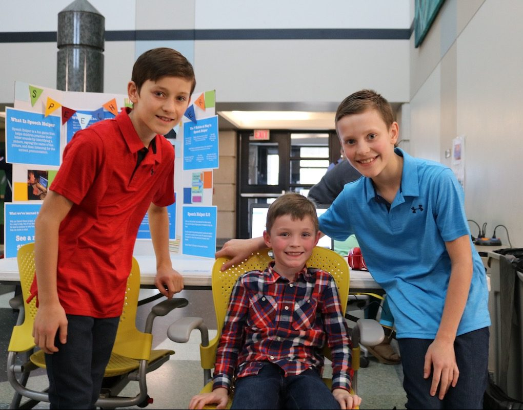 Carson (left) and McClain (right) Crigger, with Maddox, their younger brother, presenting their project, Speech Helper 2.0.