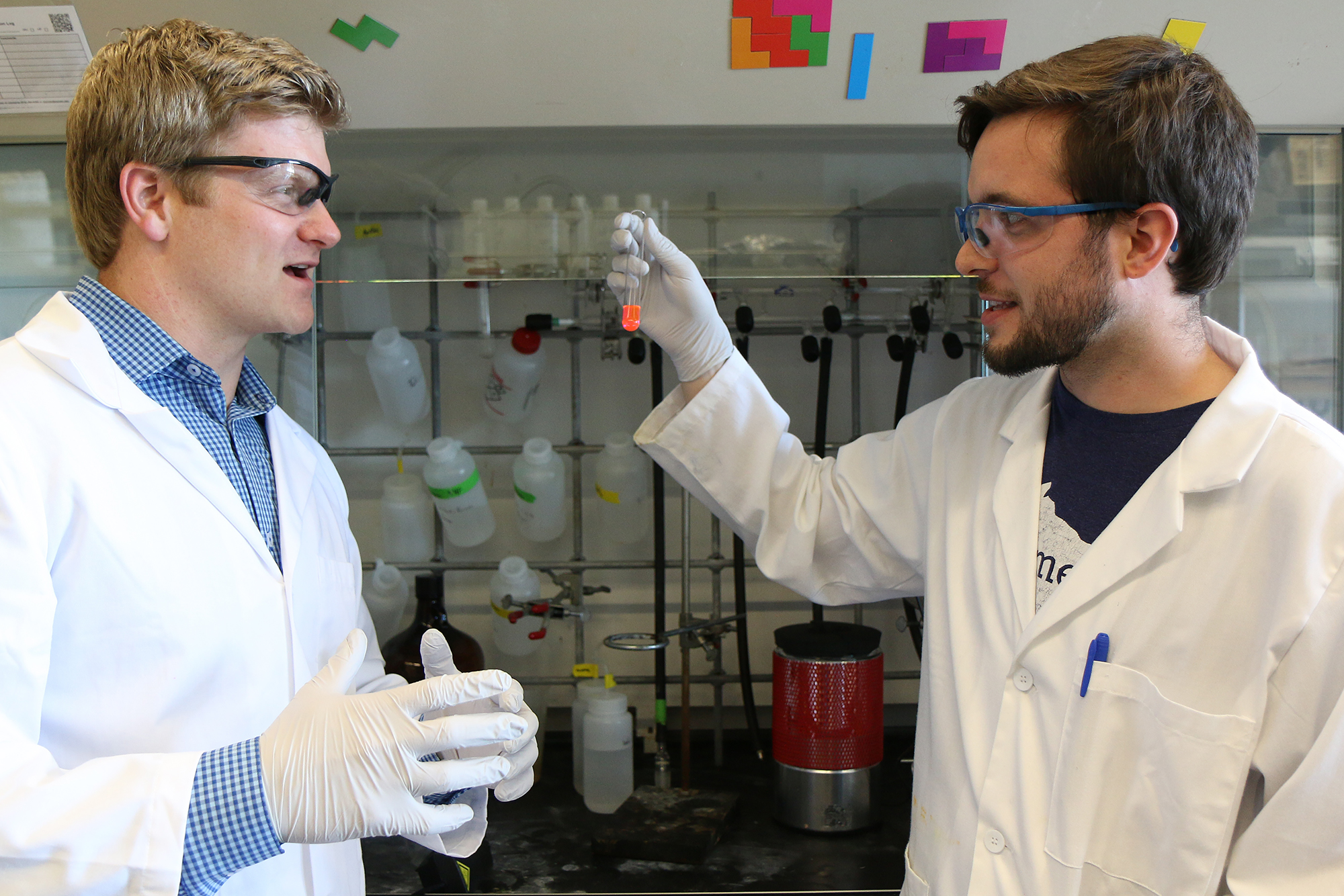 Brett VanVeller (left), assistant professor of chemistry, and Bryan Lampkin, graduate student in chemistry, look at a fluorescent chemical.
