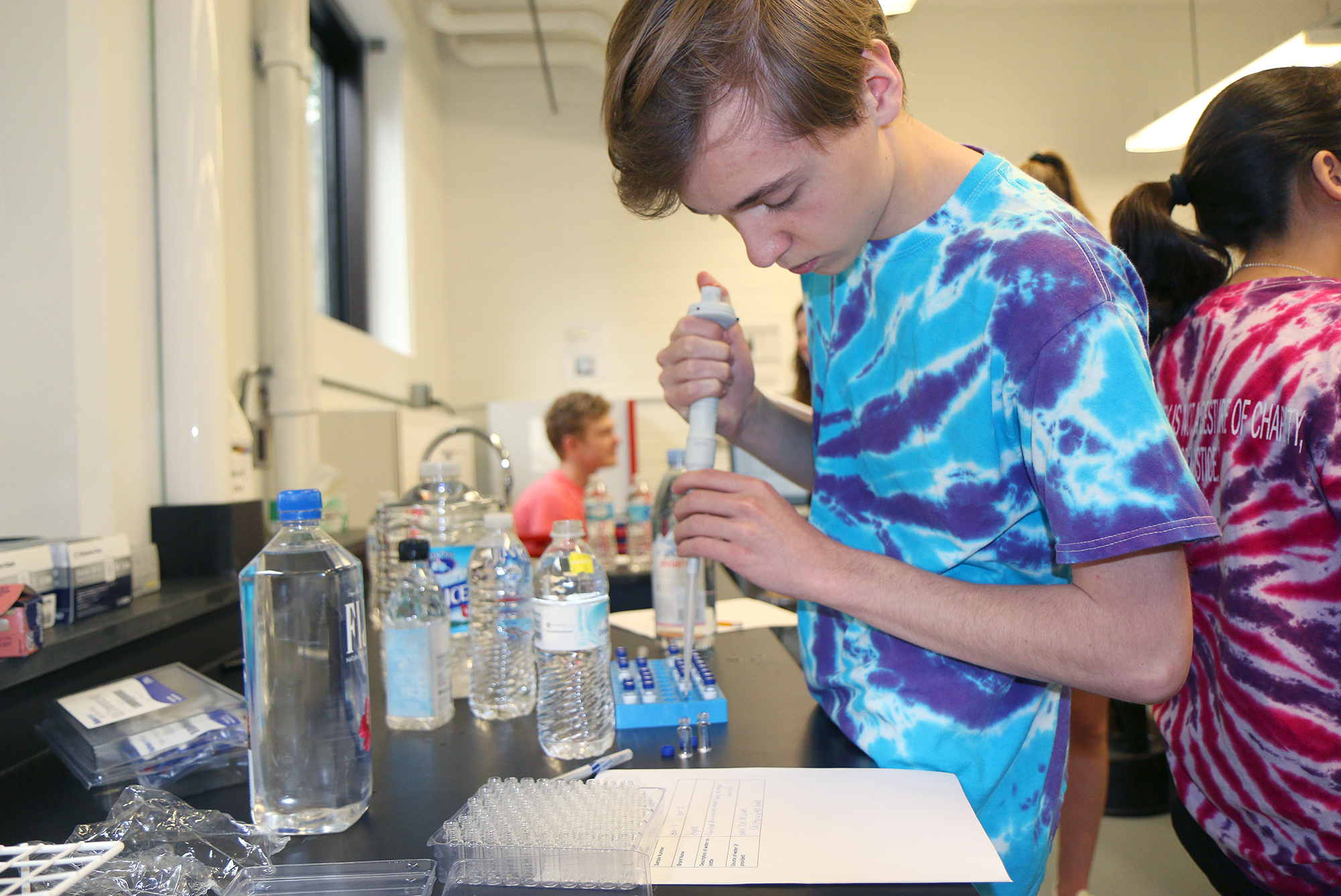 Brennan stands at a table with a large pipette and a water bottle.